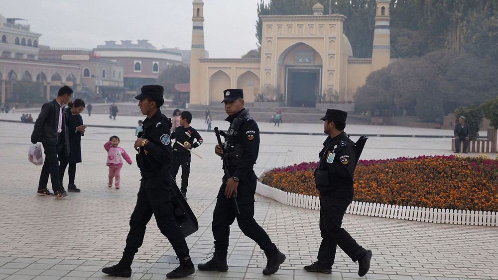 Uighur security personnel patrol near the Id Kah Mosque in Kashgar in western China's Xinjiang region in this 2017 file photo. (Ng Han Guan / Associated Press)