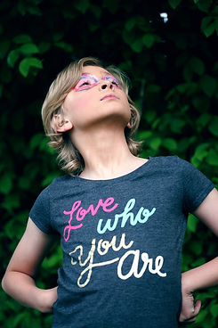 """Gender fluid child wearing t-shirt saying """"Love who you are"""""""