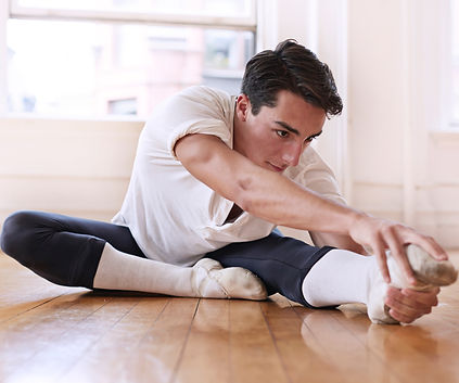 Young male stretching with ballet shoes on defying gender stereotypes