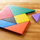 a missing piece in a square tangram puzzle, over wooden table.jpg