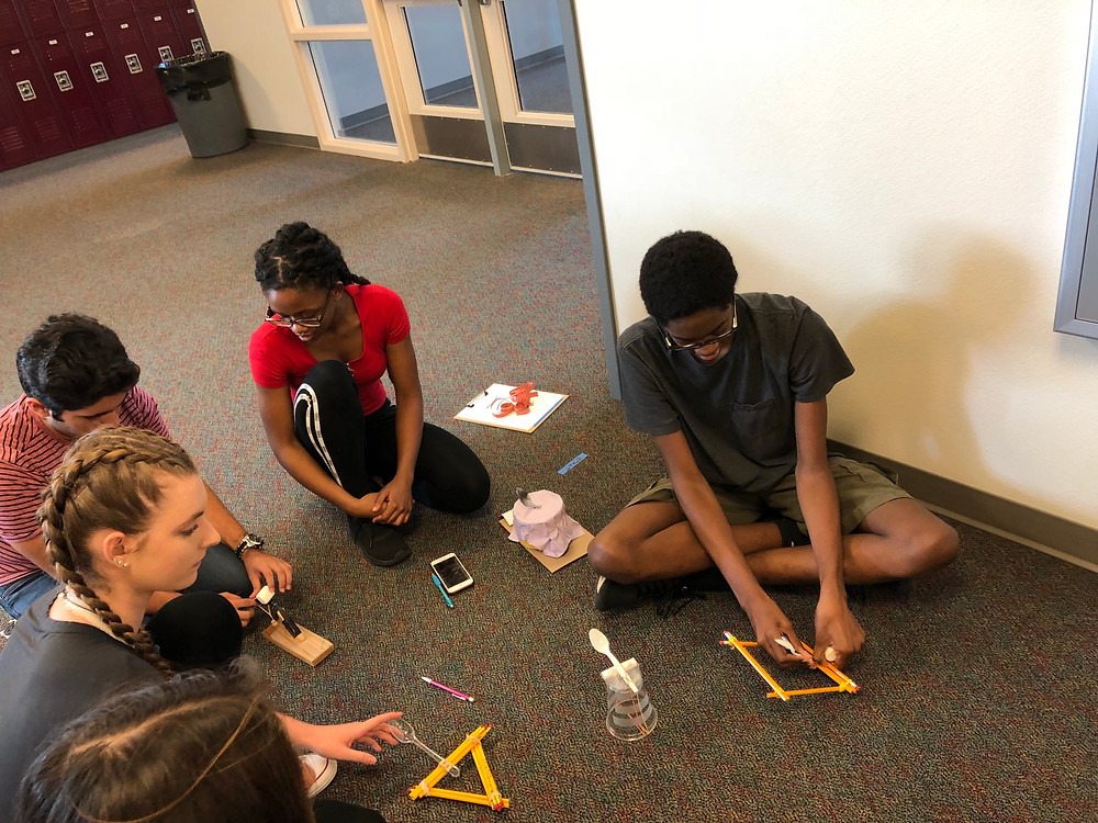 Andres Gutierrez '21, Aminata Ouattara '21 and Kallen Tyler '21 put last minute touches on their handmade catapults before putting them to work to solve math problems. Photo by Maezi Marrs '22