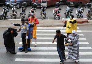 Agentes públicos fazem atividade cultural na faixa em Brasília em nome da prevenção de acidentes com pedestres.