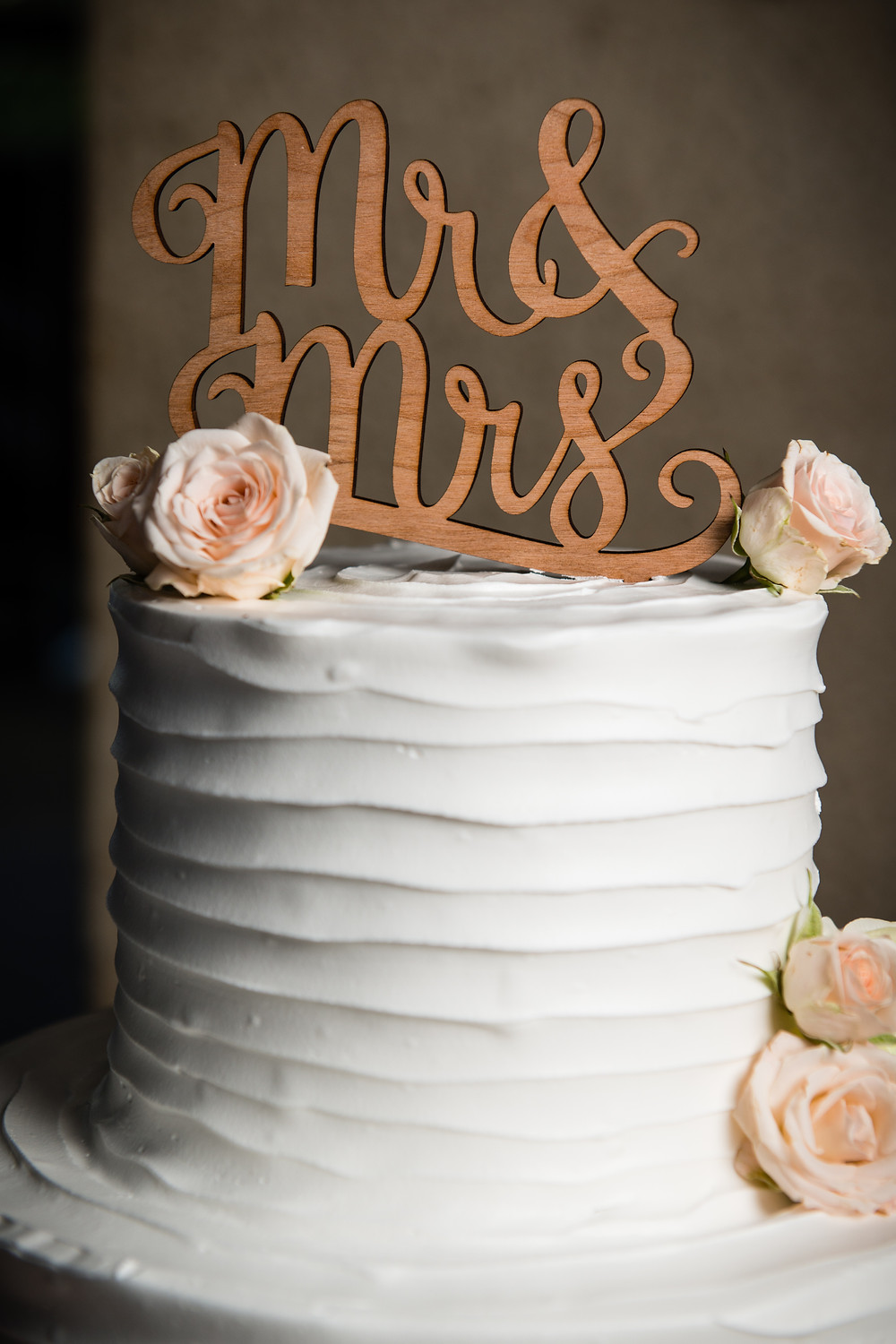 Elegant wedding cake with wooden topper Beckets Oshkosh Wisconsin Wedding Photographer Lanari Photography