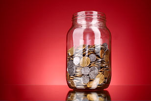 coins in money jar on red background. Uk