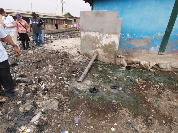 Standing floodwater mixes with trash to create a thick sludge that people come into contact with as they walk around their city.