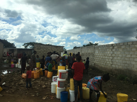 A long line gathers at a public water pump in Lusaka. The buckets are large and therefore may require several minutes each to fill up. A 5-gallon bucket full of water weighs 40 lbs (18 kg).