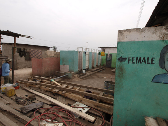 Materials and trash left out create obstacles for people using the public toilets.