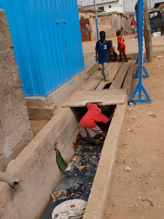 A child looks for something while standing in an open drain that contains trash and fecal matter.