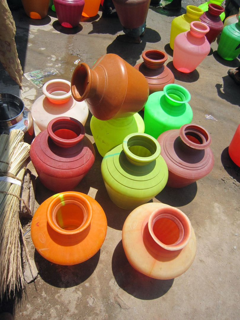 Colorful water jugs like these are used to collect water from communal water supplies. These jugs are open and do not have a lid to prevent contamination from entering the water after it is collected.