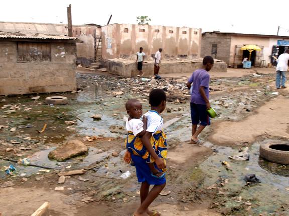 Children walking through polluted floodwater in flip flops.