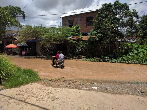 A duo crosses through floodwater on a motorcycle in Siem Reap.