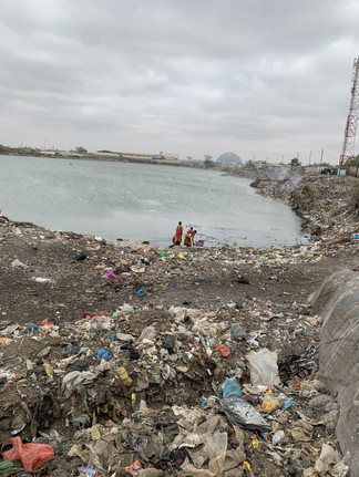 Trash and pollution accumulate near a large body of surface water in Lusaka. This water is often used for many needs, such as cooking, bathing, and drinking.