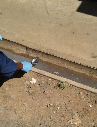 A sample is collected from an open drain.