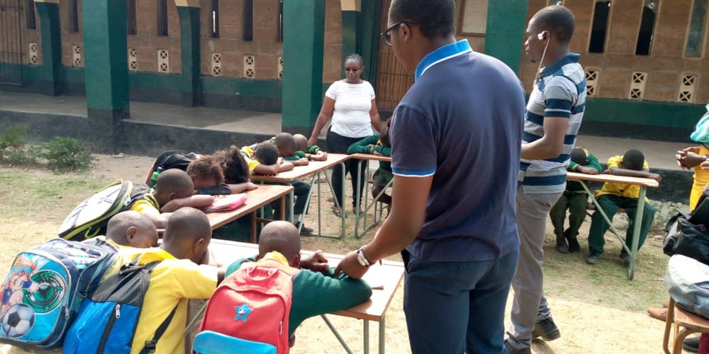 Child behavior data is collected through a school survey in Lusaka. The children keep their eyes closed and heads down so that they cannot see how other children are voting, while staff collect tokens to tally up their answers.