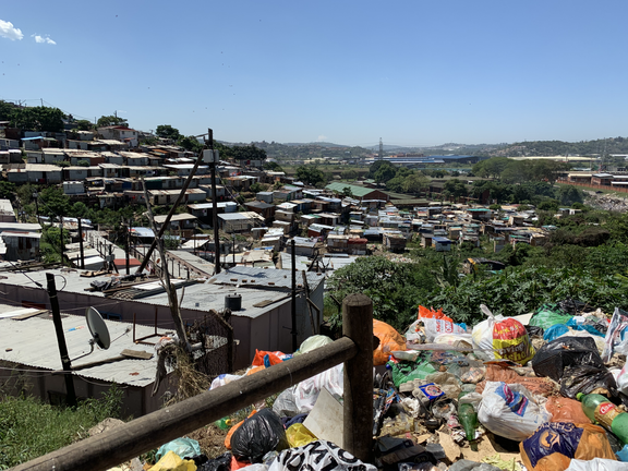 A picture of rapid urbanization in a neighborhood and trash accumulation in Durban, South Africa.