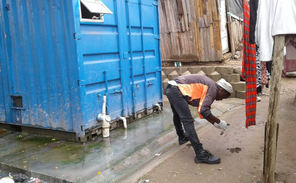 A field team member collects a soil sample outside of a public toilet facility.
