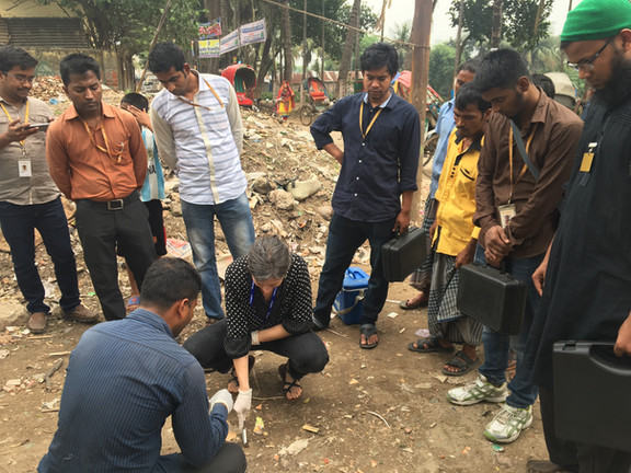 Jamie Green from SaniPath shows the Dhaka field team how to take a soil sample.