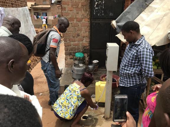 A team member demonstrates how to collect drinking water samples from a public water source in Kampala.