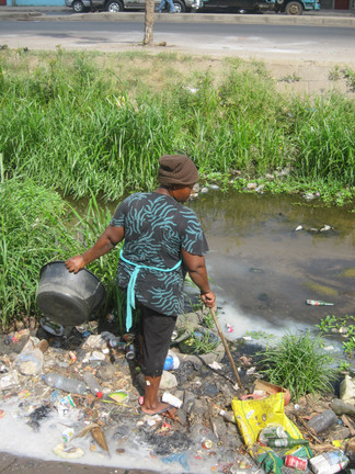 A citizen steps through pollution to gather water from an open drain in Maputo.