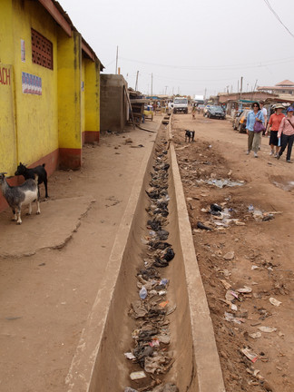 These open drains are dry but still filled with trash. Notice the goats nearby, which is typical to see in Accra. Excrement from animals also leads to fecal exposure in the environment.