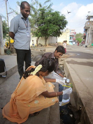 An open drain sample is collected by field staff in Vellore.