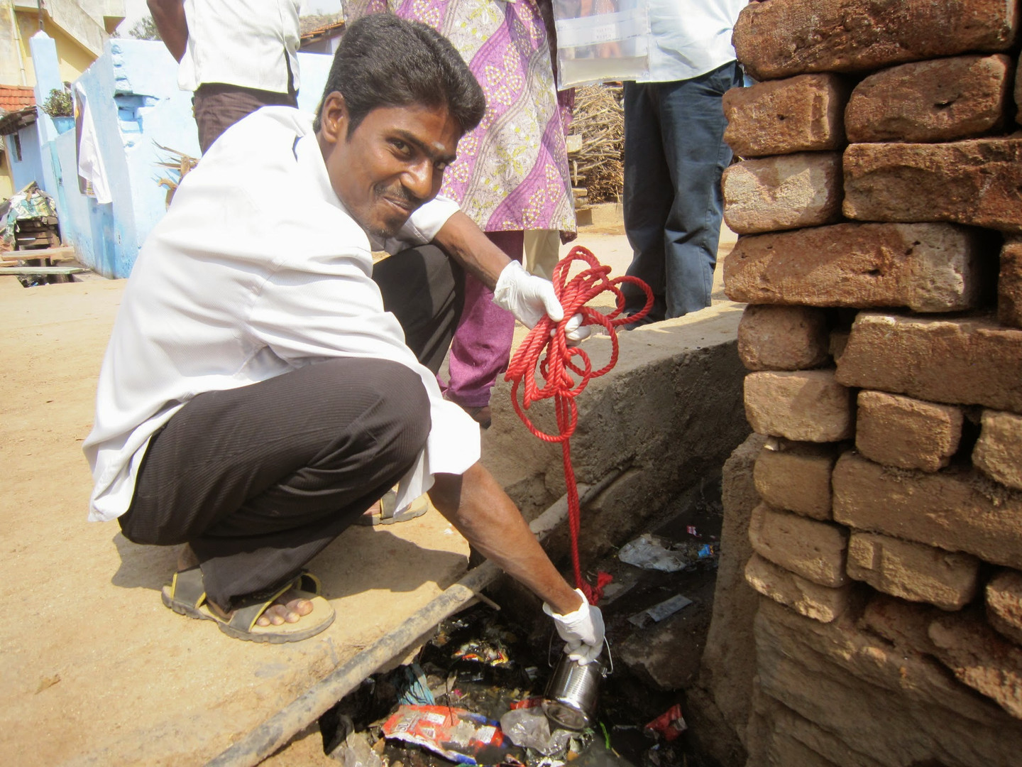 A team member smiles for the camera and he collects a sample from an open drain in Vellore.