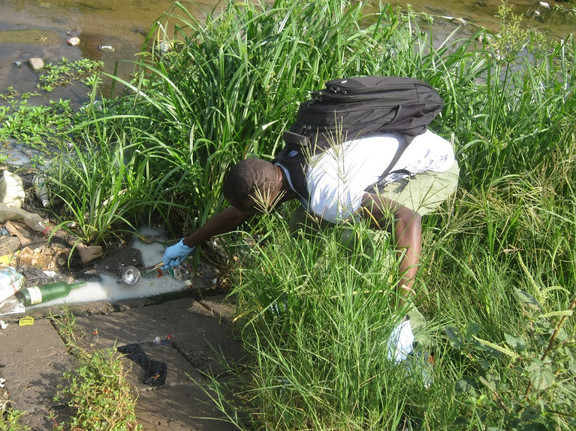 A field staff member reaches for a sample from this open drain.