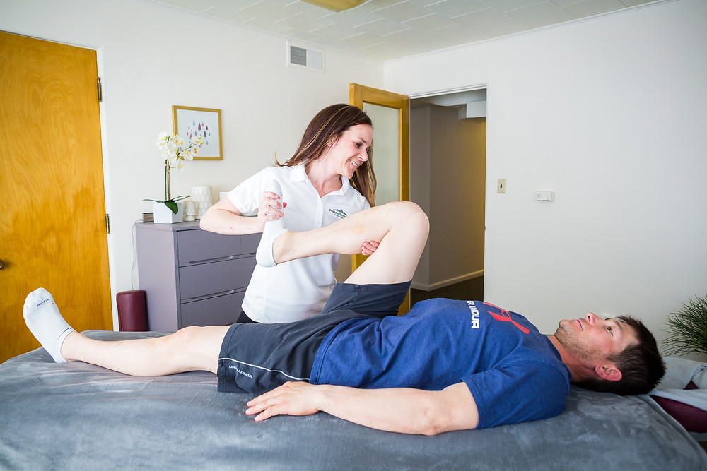 Traci Aguilar stretching client during sports massage session