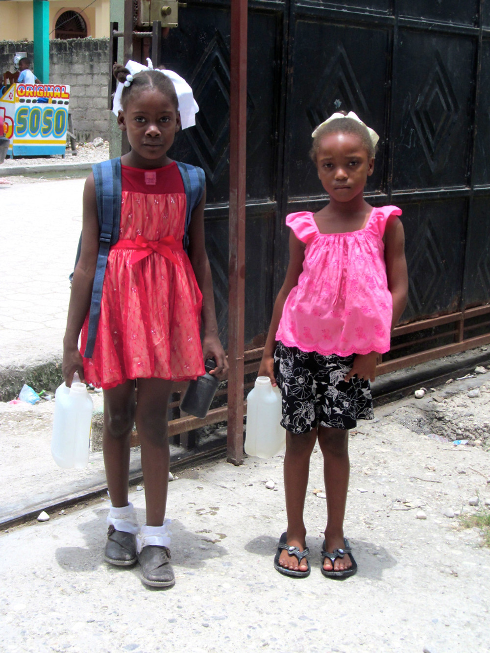 Little girls carrying small jugs to the community water spigot!