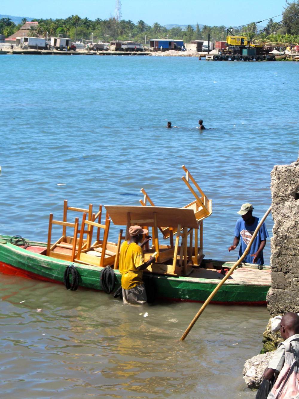 Desks are loaded onto the little ferry boat that will take them to the bigger boat waiting further out in the sea!