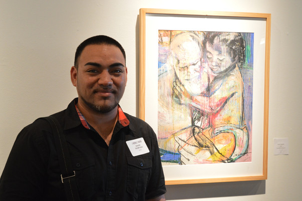 artist Saumo Puapuaga in front of his work