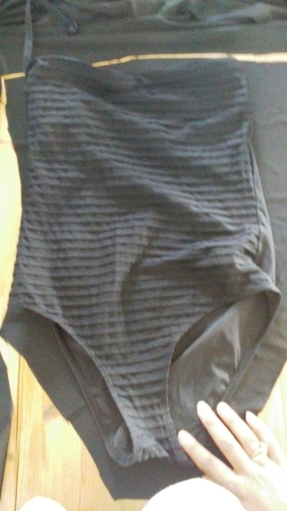 Laying a swimming costume over the fabric as a template