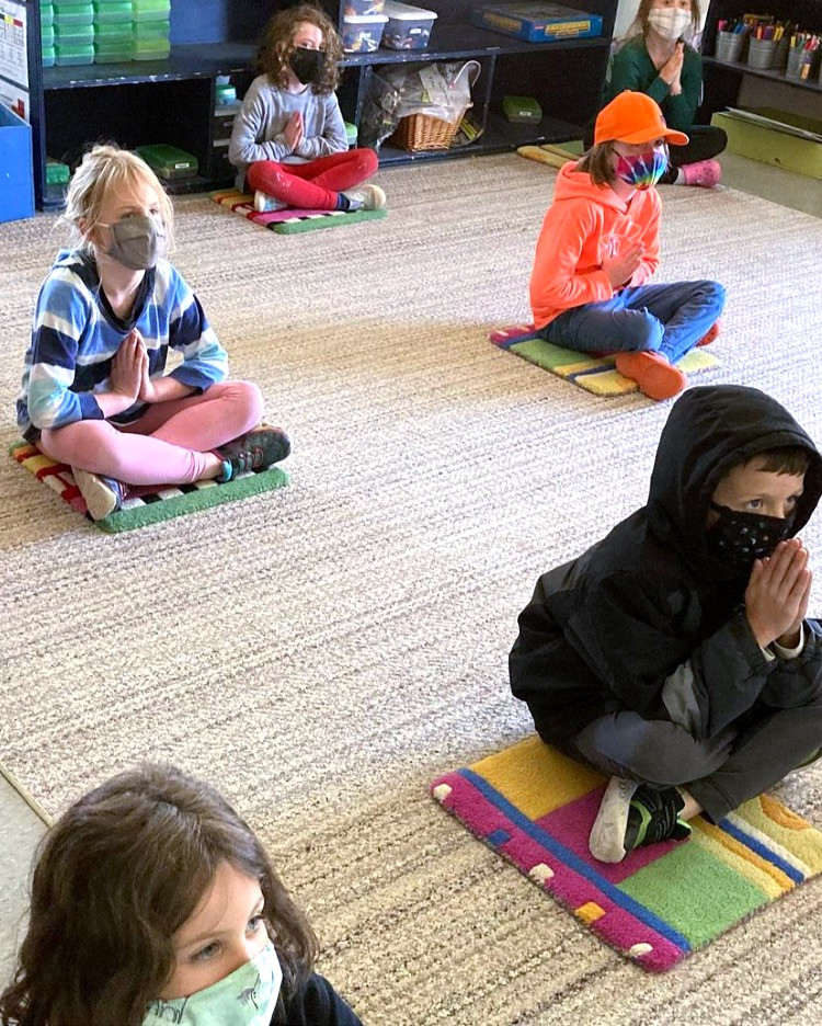 Children sitting on run with hands clasped performing mindfulness practice
