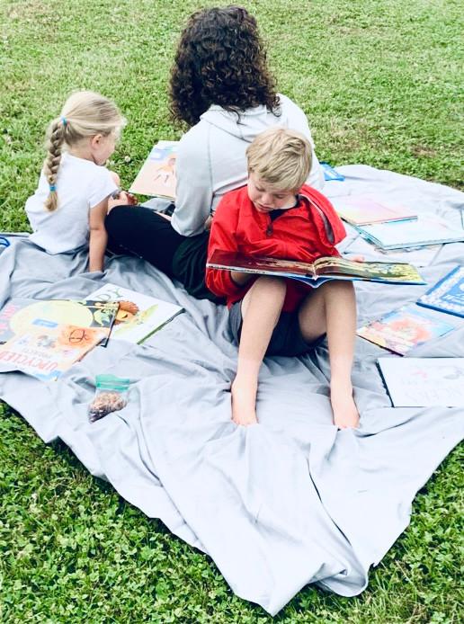 Kids & Teacher Reading on blanket: FernLeaf Community Charter School 2021 Summer Reading List for all ages