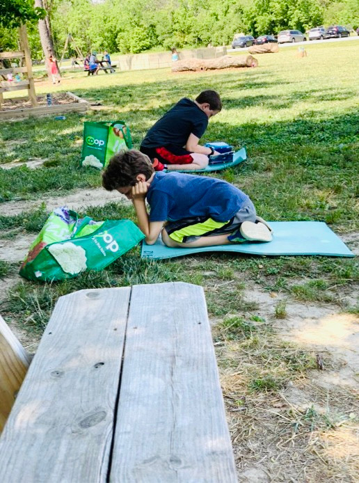 Boys reading on lawn: FernLeaf Community Charter School 2021 Summer Reading List for all ages