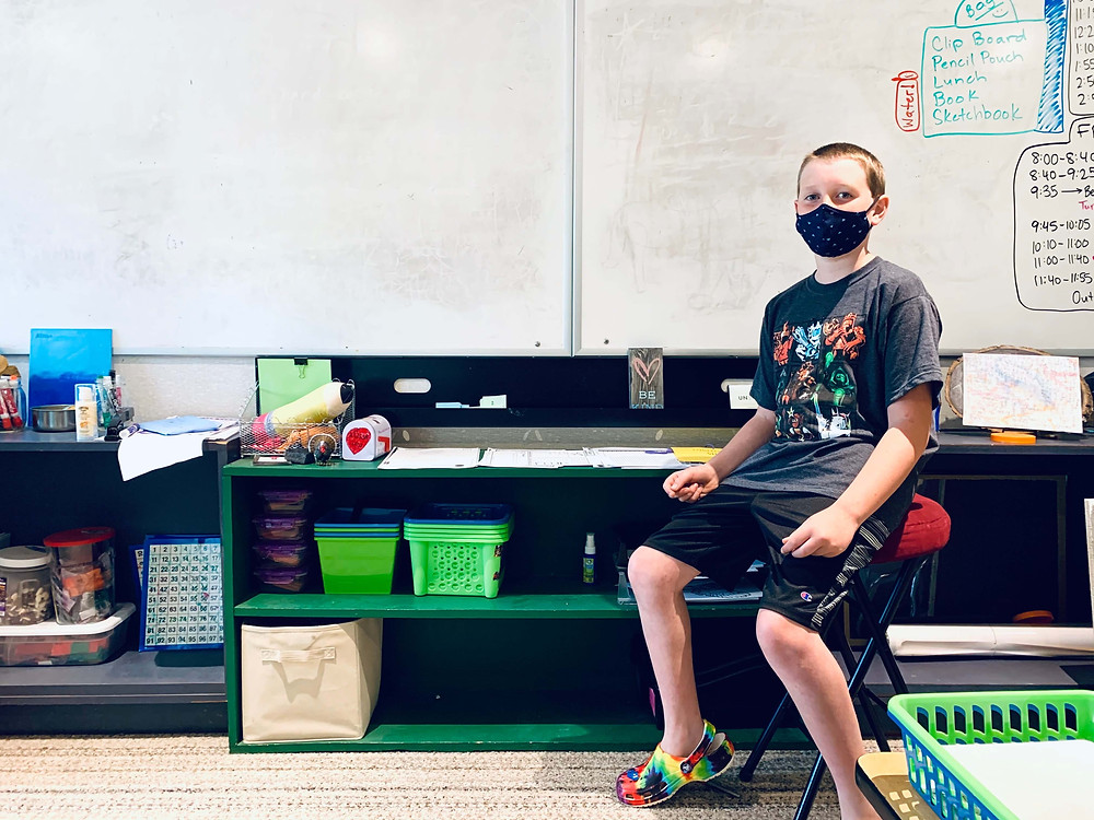 child sitting in front of class posing next to recycled shelves he created