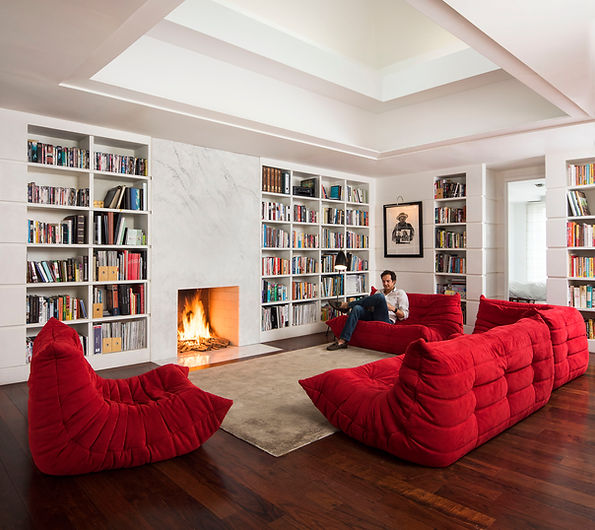 View of library in residence in Guatemala with marble fireplace and cozy living