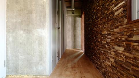 【玄関廊下の壁】壁一面に貼り付けられたチーク古材のアクセントウォールとコンクリート素地。豊かな凹凸やアンティークカラーが楽しめます。ロッジに来たような、非常にインパクトの強い壁です。