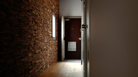 【玄関】玄関廊下側の景色。ドアの色、通路に敷いた無垢材、壁の色がとてもマッチしています。