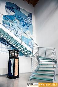 Una scala che accosta un muro con un rivestimento RPM Italia in diverse tonalità di azzurro