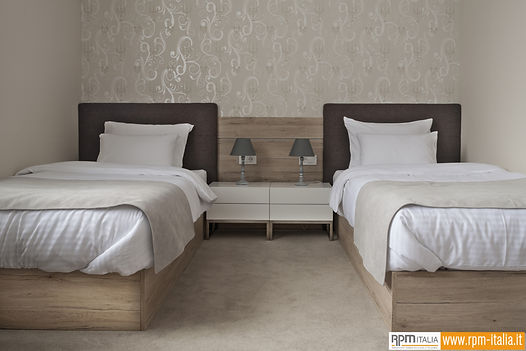 Una stanza di un hotel con due letti e pareti rivestite di resina con finitura effetto legno