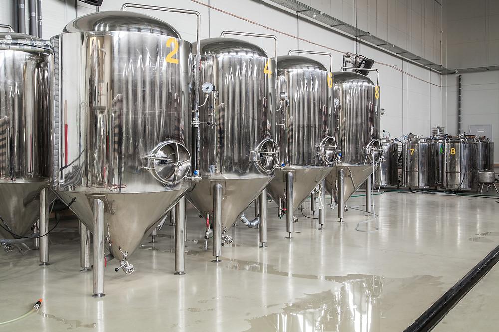 Numerosi serbatoi in acciaio all'interno dell'ambito produttivo di una azienda vitivinicola. Il pavimento in resina è igienico ed antibatterico, nonostante ci sia uno sversamento biologico sul pavimento.