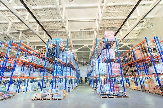 Un magazzino con molti pallets e merce con pavimenti in resina color grigio