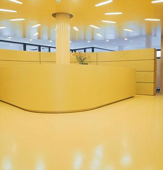 Uno studio con pavimenti e rivestimenti in resina monocromatica gialla ed un mazzo di fiori sul bancone della reception