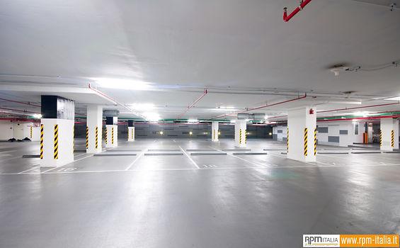 Un parcheggio interrato con pavimenti in resina color grigio e segnaletica di delimitazione bianca e segnaletica di pericolo su delle colonne portanti bianche