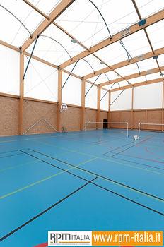 Un'impianto sportivo con pavimentazioni in resina color azzurro, segnaletica color giallo, rosso e nero ed una rete per giocare a tennis