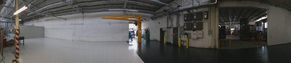 Officina metalmeccanica con quadri di controllo, tubi ed una gru