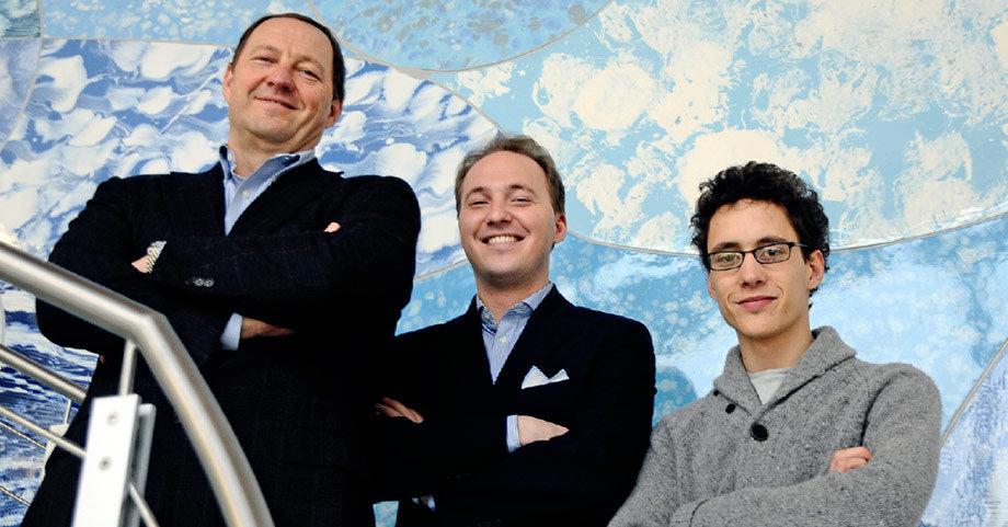 Un padre con i suoi due figli sorridenti nell'azienda di famiglia