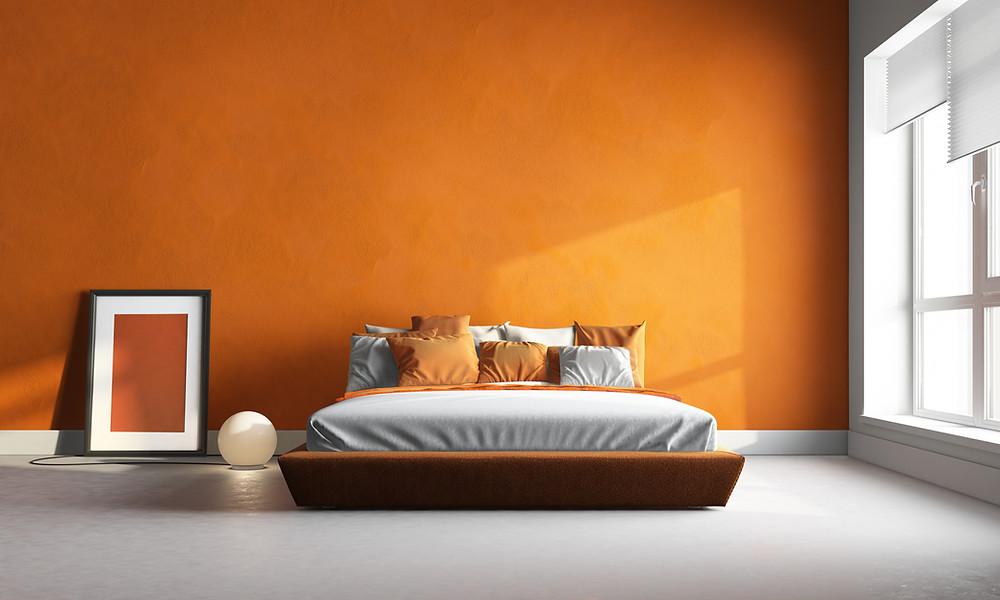 Una camera da letto moderna e con pareti arancioni e grigie. Una lampada accesa ed una finestra da cui entra il sole illuminano pareti e pavimenti in resina