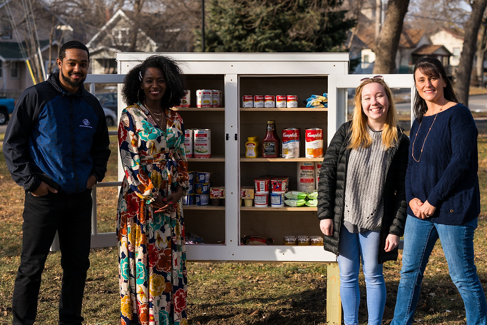 The Boys & Girls Club team stands in front of their first fully stocked Little Free Pantry.